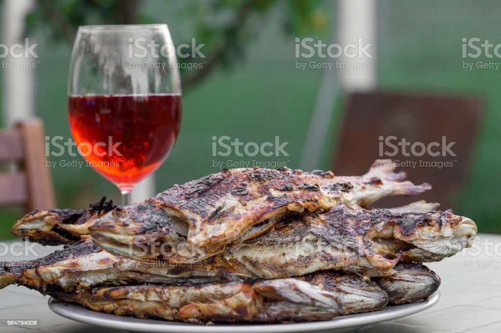 Heap of fresh grilled trout on plate and one glass filled with red wine in background royalty-free stock photo
