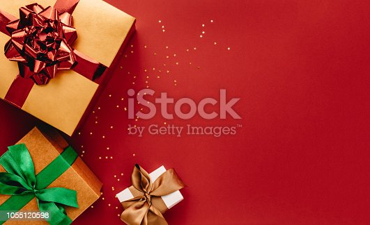 Heap of gift boxes and stars confetti on red background. Flat lay composition for christmas with copy space.