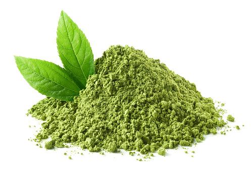 Heap of green matcha tea powder and leaves