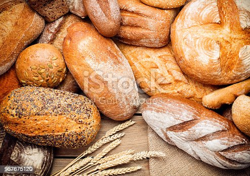 heap of various loafes of bread on wooden background
