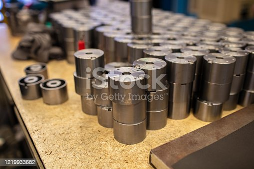 Close-up of heap of machined round metal couplings on production line