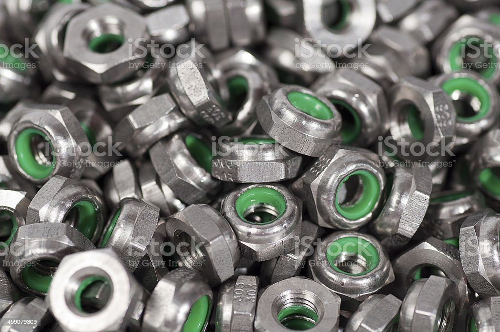 heap of metal nuts with green interior, stacked stock photo