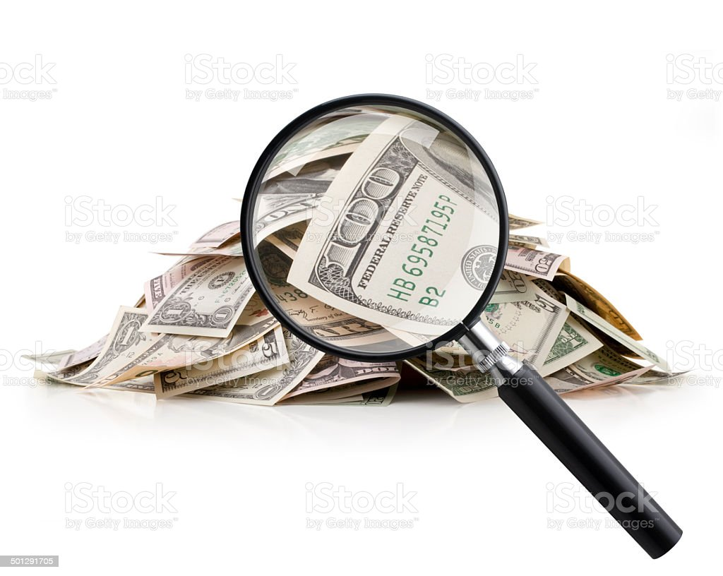 Heap of money with magnifying glass stock photo