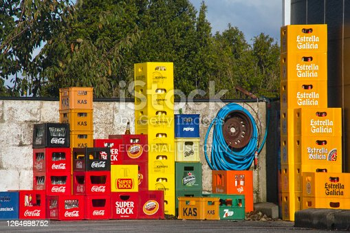 Oleiros, Galicia, Spain- October 21, 2019 : Group of stacks of multi colored plastic crates for beverage bottles, seen on a city street sidewalk outside a bar. Several beer, soda and soft drink brands on them. Coiled hose, concrete wall and green tree laeves in the background.
