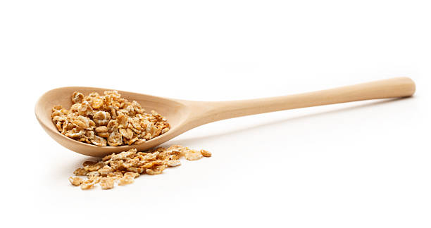 Heap of oat flakes with wooden spoon stock photo