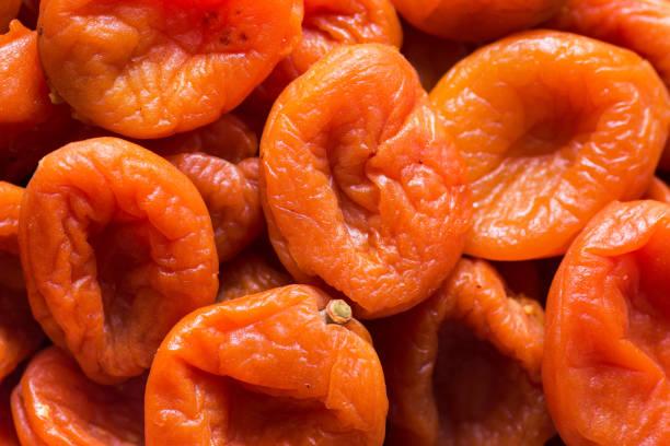 haufen von bio-trockenfrüchten dehydrierte aprikosen. gesunde ernährung vollteile vegan konzept. kreatives food-plakat tapete - orangenscheiben trocknen stock-fotos und bilder