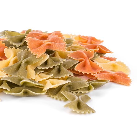Heap of pasta farfalle tricolore. Close-up. Whole background. It is located on a white surface.
