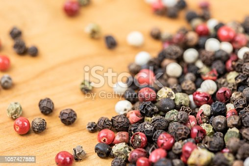 Heap of pepper in color on wooden table.