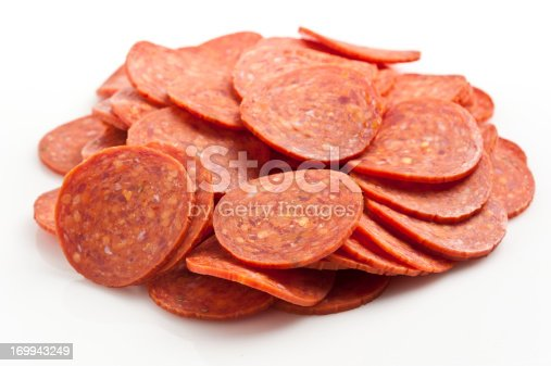 Heap of pepperoni on white background
