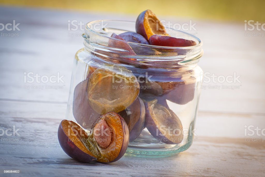 Heap of plums in glass jar on wooden table royalty-free stock photo