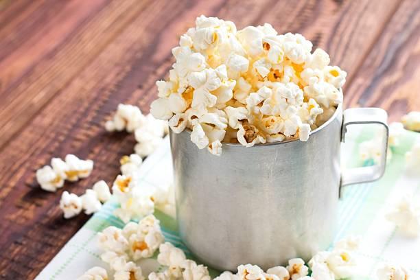 heap of popcorn in aluminum cup - zout smaakstof stockfoto's en -beelden