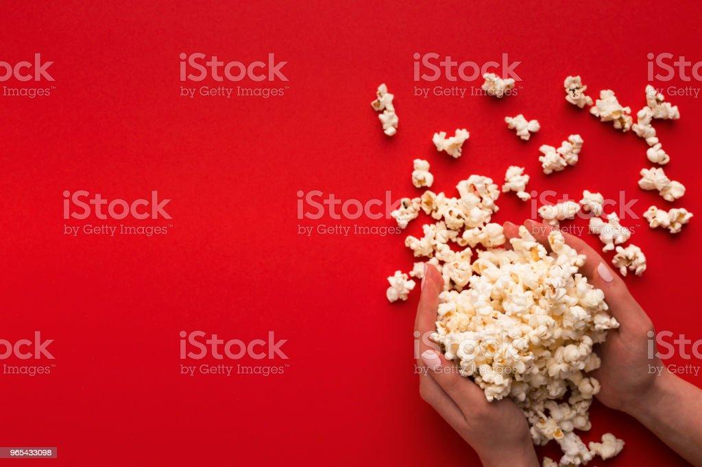 Tas de pop-corn en mains sur fond rouge, vue de dessus - Photo de Activité avec mouvement libre de droits
