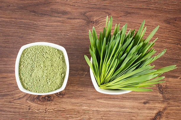 Heap of powder barley and barley grass on wooden background stock photo
