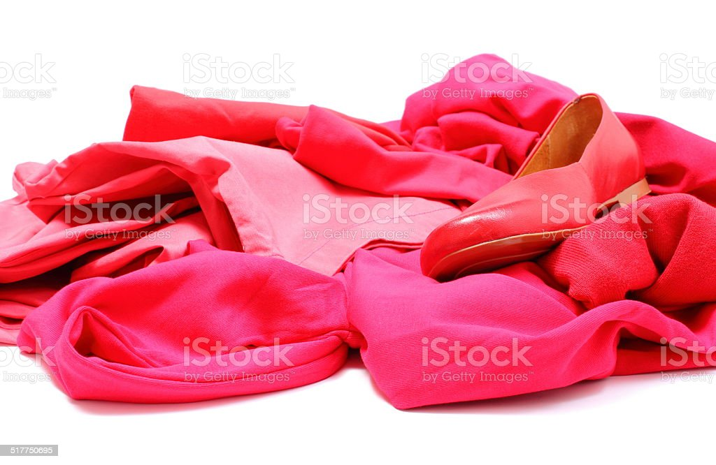 Heap of red and pink clothes with womanly shoes stock photo
