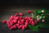 Freshly picked raspberries with leaves on a wooden table. Heap of red fresh raspberries.