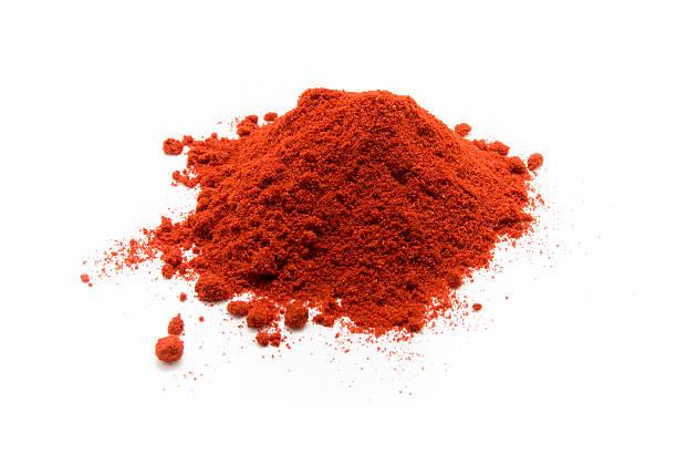 heap of red paprika powder on a white background - paprikapoeder stockfoto's en -beelden