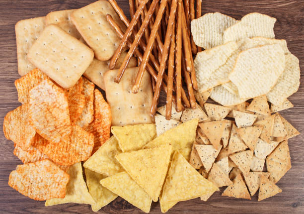 Heap of salted crisps, breadsticks and cookies, concept of unhealthy food stock photo