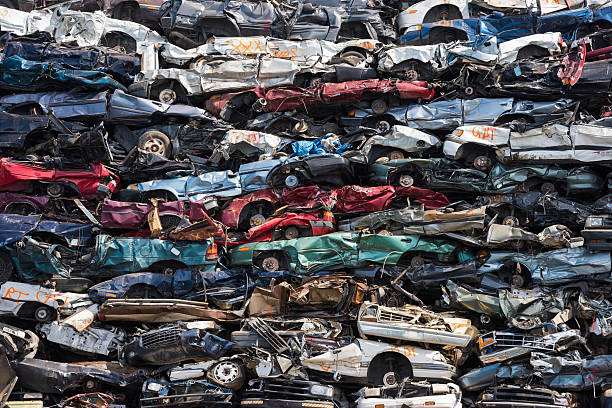 Heap of scrap cars Crushed cars stacked up for recycling crushed stock pictures, royalty-free photos & images
