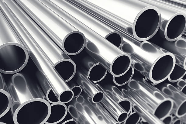 Heap of shiny metal steel pipes with selective focus effect stock photo