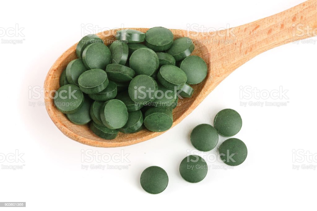 heap of Spirulina tablets algae nutritional supplement in wooden spoon isolated on white background close up top view stock photo