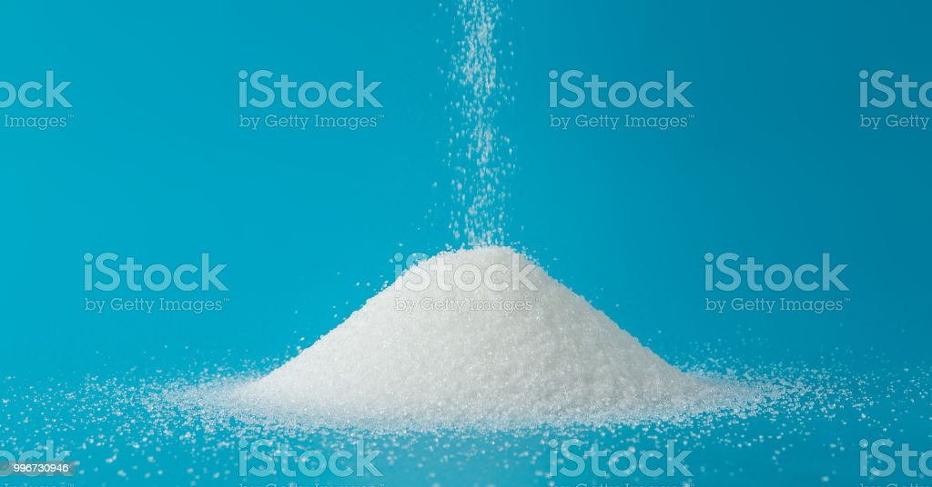Heap of sugar with pouring on blue background royalty-free stock photo