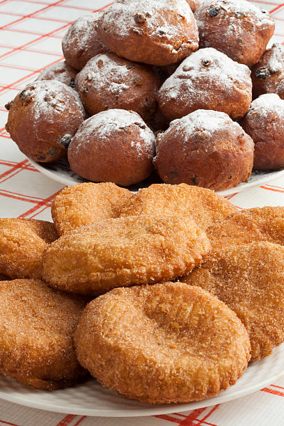 heap of sugared fried fritters called oliebollen and appelflapp - oliebollen stockfoto's en -beelden