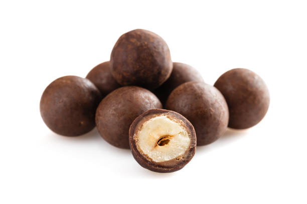 Heap of sugared hazelnuts dragees in chocolate isolated on white background stock photo