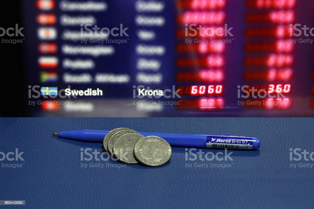 Heap of Sweden coins with blue pen on the blue floor and digital board of currency exchange money background. - Zbiór zdjęć royalty-free (Biznes)