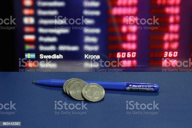 Sterta Szwedzkich Monet Z Niebieskim Długopisem Na Niebieskiej Podłodze I Cyfrowej Tablicy Wymiany Walut Tła - zdjęcia stockowe i więcej obrazów Moneta