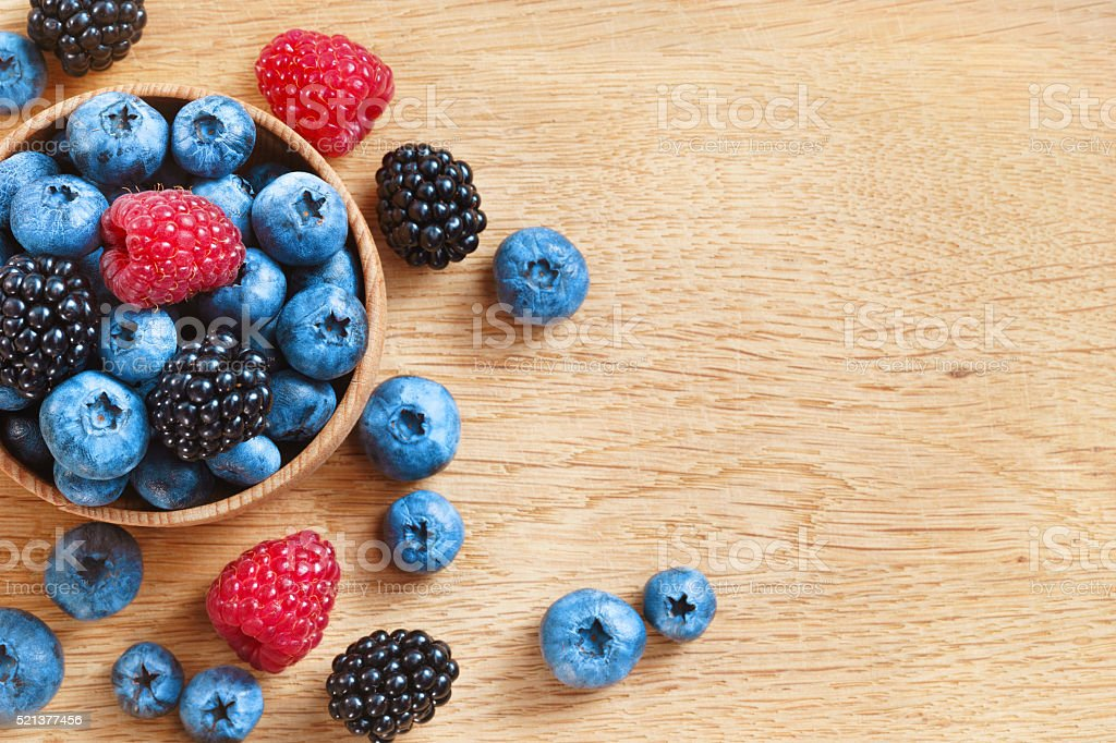 Heap of sweet tasty berries on wooden table. stock photo