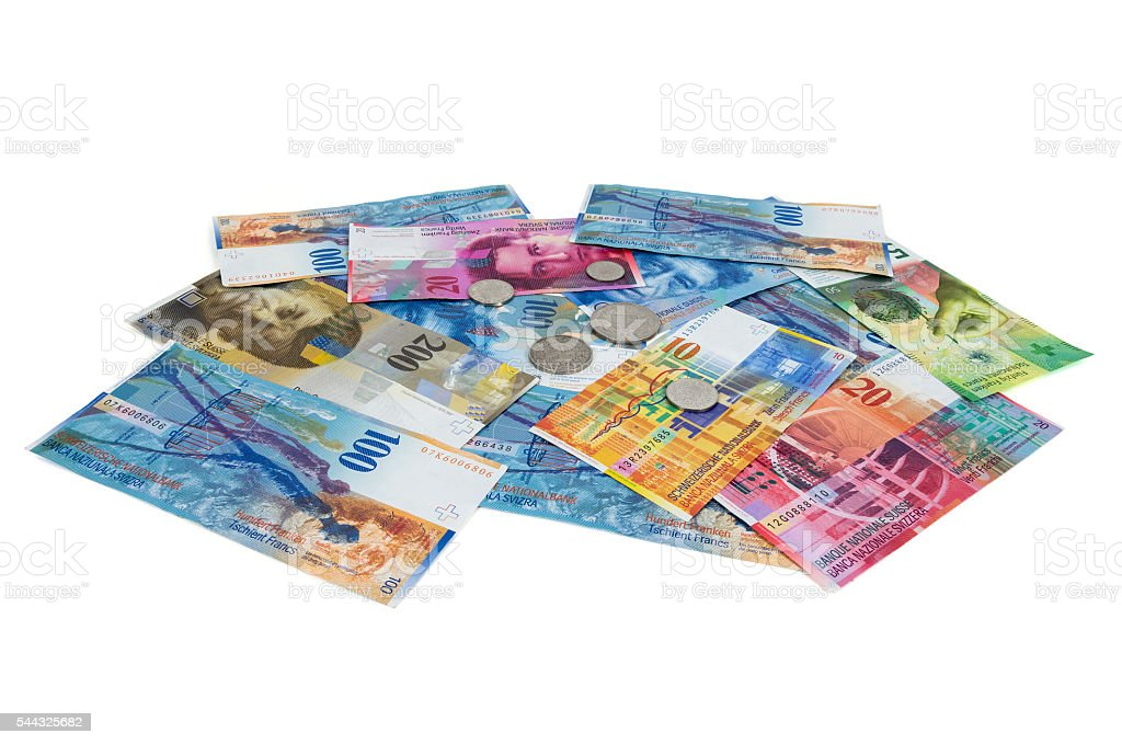 Heap of swiss franc banknotes and coins on white background stock photo