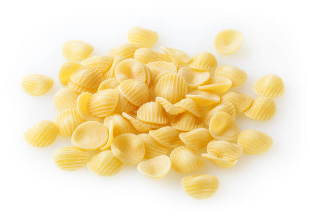 Heap of uncooked orecchiette pasta isolated on white background Heap of uncooked orecchiette pasta isolated on white background orecchiette stock pictures, royalty-free photos & images