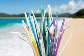 Heap of used plastic straws on background of clean beach and ocean waves. Plastic ocean pollution, environmental crisis. Say no plastic. Single-use plastic waste