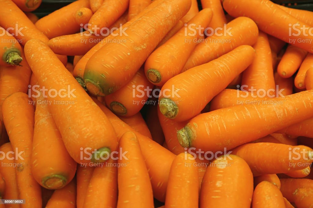 Heap of vibrant orange color carrots, for background or banner stock photo