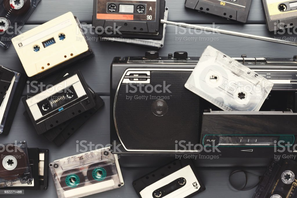 Heap of retro audio cassettes and vintage tape recorder on gray...