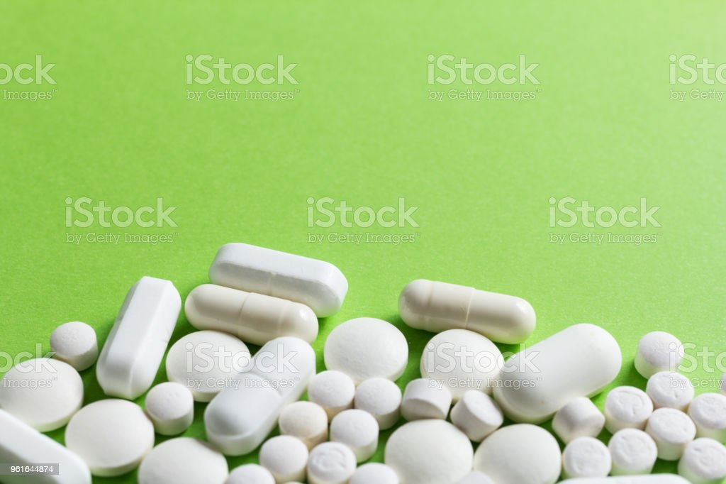 Heap of white capsules on green table. stock photo