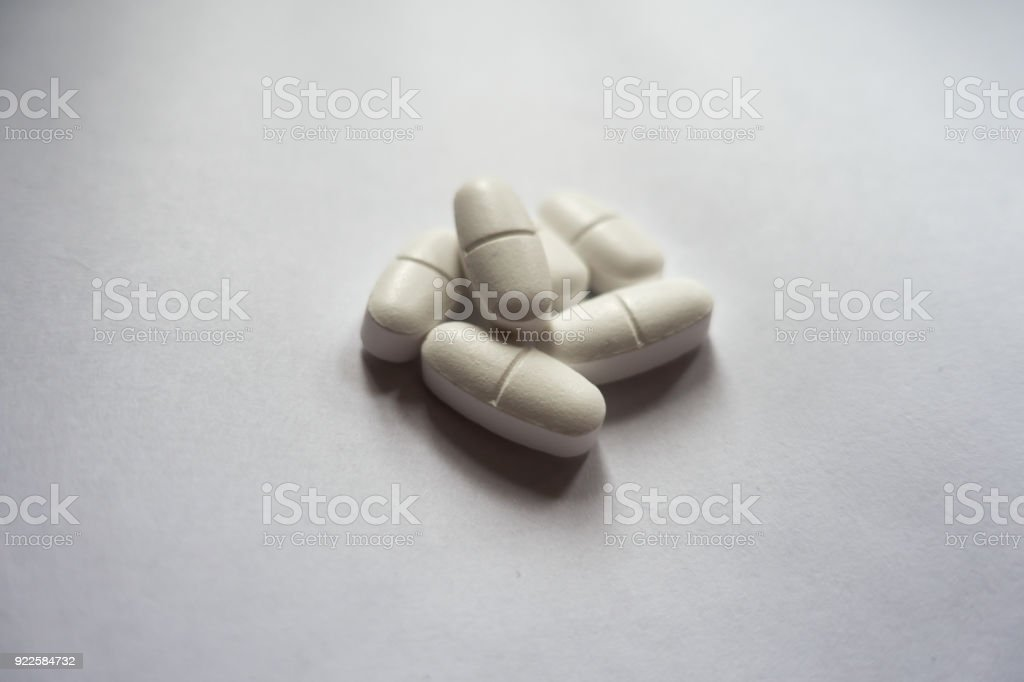 Heap of white oblong caplets of calcium citrate stock photo