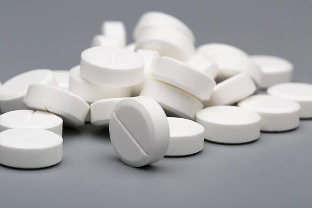 Heap of white round pills medical stock photo