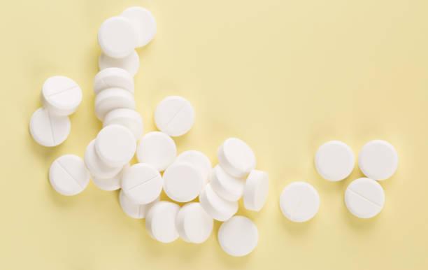 Heap of white round pills stock photo