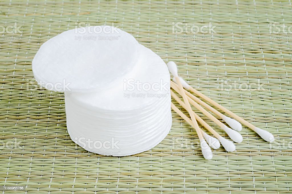 Heap of wood stick cotton buds and stack of cotton pads on a...