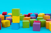 Heap of wooden toy blocks on blue background.