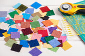 Heap square pieces of colorful fabrics on white wooden surface, quilting accessories