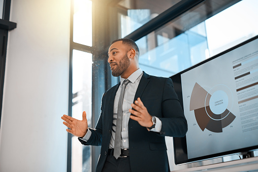 Shot of a young businessman presenting data on a screen during a meeting in an office