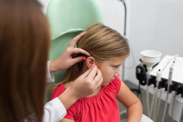 hearing aid checkup in otolaryngologist's office stock photo