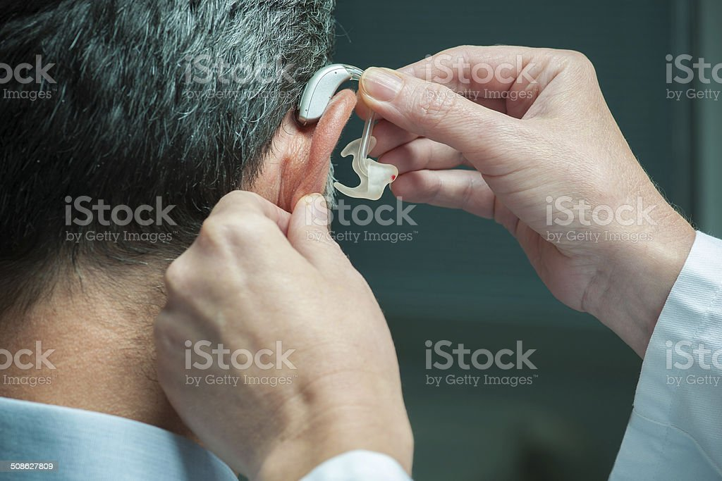 Hearing Aid Doctor inserting hearing aid in man's ear A Helping Hand Stock Photo