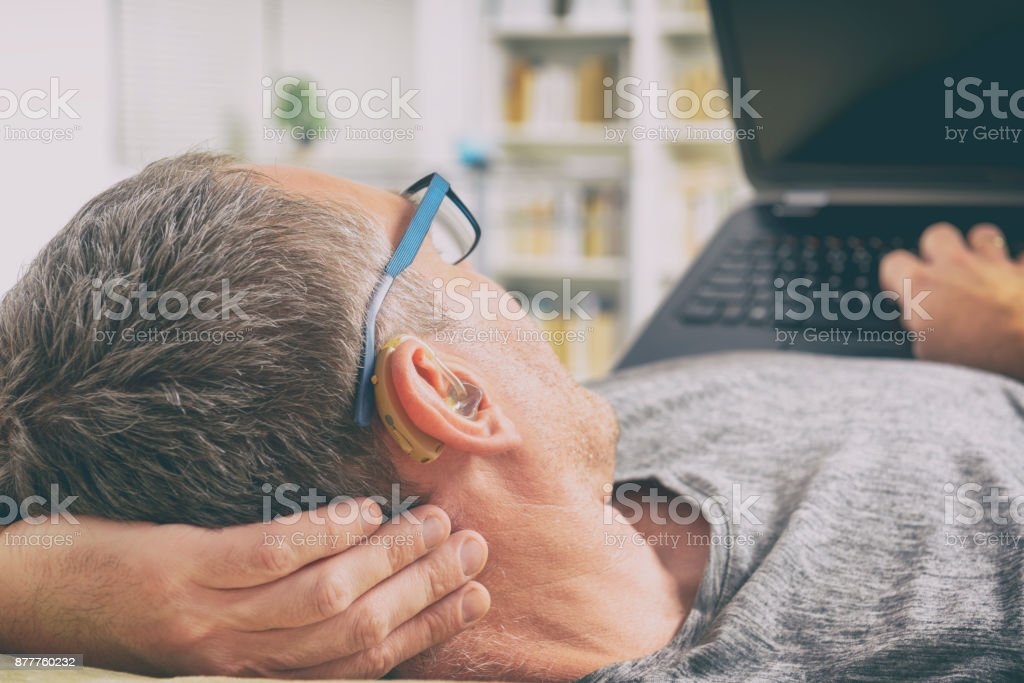 Hearing impaired man using laptop stock photo