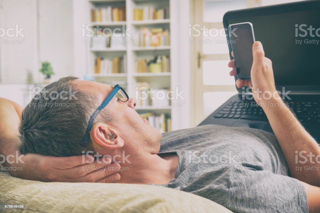 Hearing impaired man with laptop and mobile phone stock photo
