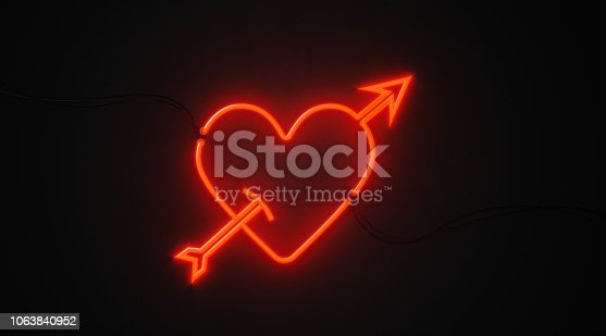 Heart and arrow shaped red neon light on black wall. Horizontal composition with copy space. Great use for Valentines Day and Cupid concepts.