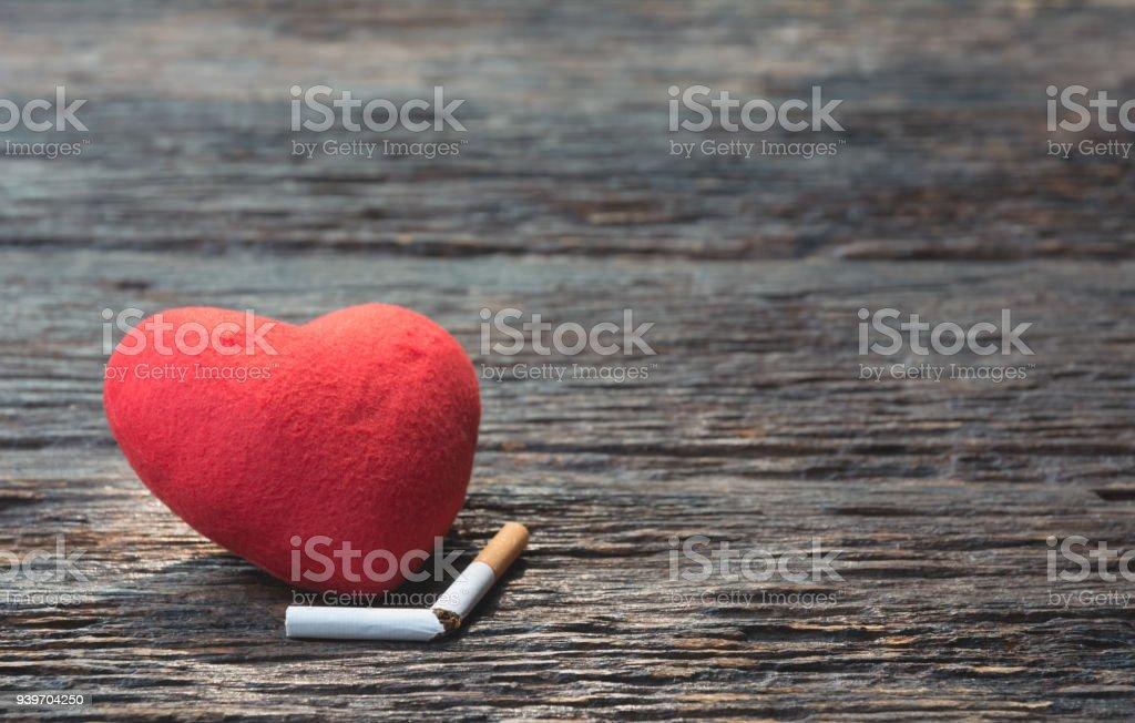 Herz und Cut-off-Zigarette auf hölzernen Hintergrund. Schützen Sie Ihre Gesundheitskonzept. – Foto