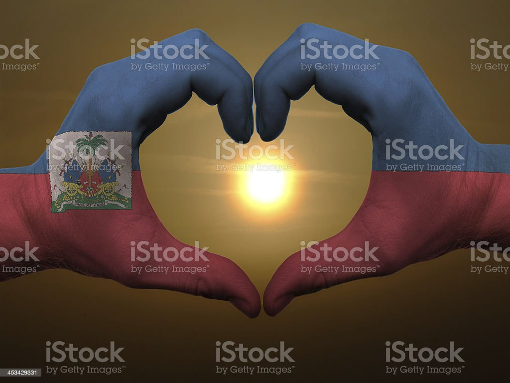 Heart and love gesture by hands colored in haiti flag stock photo